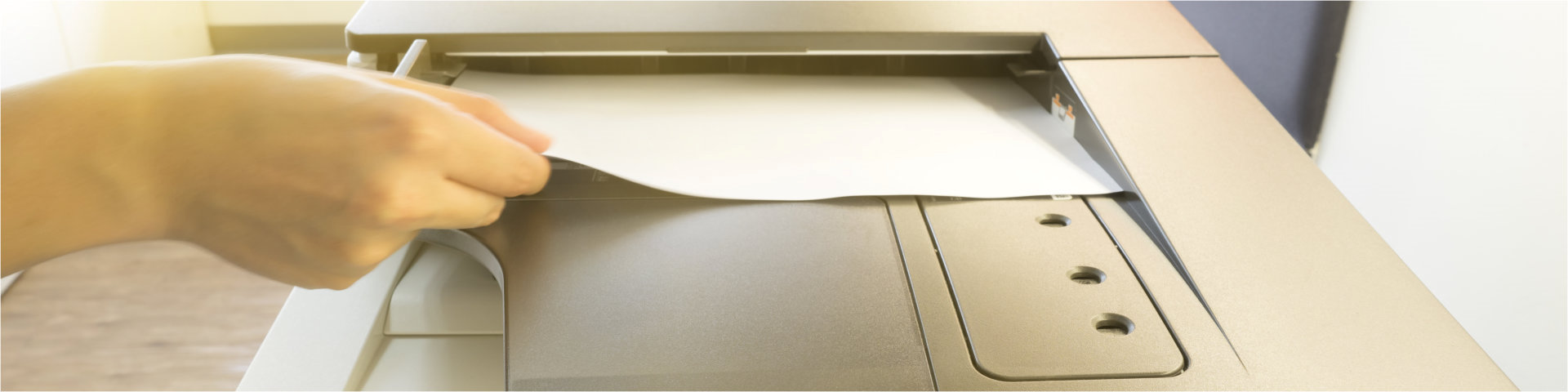 crop image of a person putting a paper inside photocopier machine